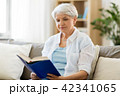 senior woman reading book at home 42341065