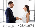 businesswoman and businessman shake hands 42341074