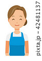 青いエプロンを着用した女性が微笑んでいる 42481137