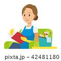 青いエプロンとゴム手袋を着用した女性がソファーに座って読書をしている 42481180