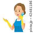 青いエプロンとゴム手袋を着用した女性がスマートフォンで通話している 42481186