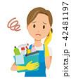 青いエプロンとゴム手袋を着用した女性が掃除道具を持って困っている 42481197