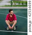 Smiling guy dressed in shirt sitting on skateboard 42534699