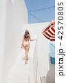 girl in bikini stands against white house 42570805