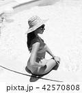girl in bikini stands against white house 42570808