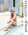 girl in bikini stands against white house 42570810