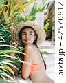 girl in bikini stands against white house 42570812