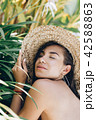 young attractive brunette woman under a palm tree 42588863