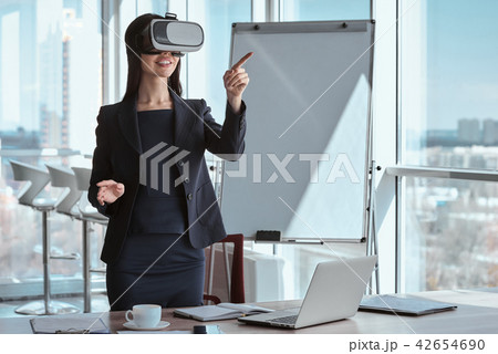 Businessperson at office alone standing wearing virtual reality  42654690