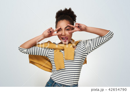 Young woman studio isolated in white making mask with hands wink 42654790