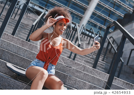 Young woman in visor and earphones free style on the street sitt 42654933