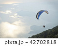 Parachute flying in clouds at top of mountains 42702818