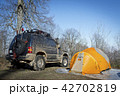 Tents and SUV car in forest at sunrise 42702819