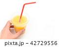 オレンジスムージーの入った飲み物のプラスチック容器とストロー 42729556