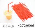 オレンジスムージーの入った飲み物のプラスチック容器とストロー 42729596