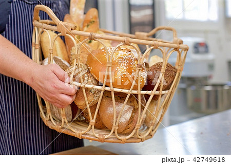 Baker holding basket of bread in the kitchen of the bakery 42749618