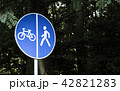 Blue bicycle and walk lane sign with trees background 42821283