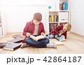 Three years old child sitting among books at home 42864187