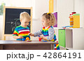 Little child playing with toys in kindergarten 42864191