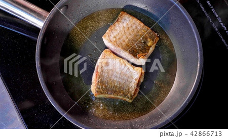 Pan-fried fish, Two pieces of loban fillet on the steaming frying pan. 42866713