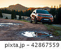 SUV on a country road in mountains at sunrise 42867559