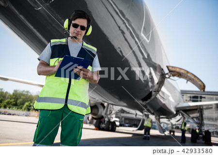 Airport worker filling out documents while ground crew members checking plane before the flight 42933580
