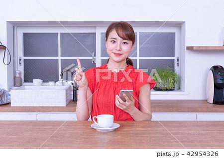 珈琲を飲みながらスマホを見る女性 42954326