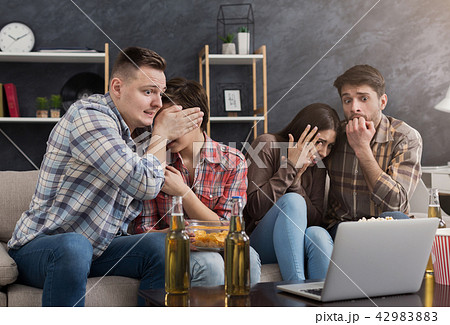 Multiracial group of frightened friends watching film 42983883