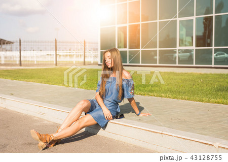 Lifestyle, fashion and people concept - Portrait of a beautiful young woman with long hair sitting 43128755
