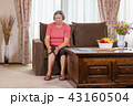 Elderly woman suffering from pain in knee at home 43160504