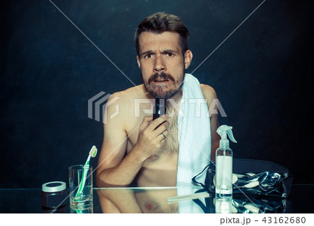 young man in bedroom sitting in front of the mirror scratching his beard 43162680