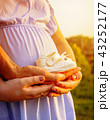 Close-up pregnant woman's belly with baby shoes, concept of lovely future parents 43252177