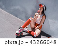 Happy beautiful young woman riding on rollers, eating candy. Summer photo. 43266048