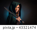 Mysterious young woman keeping sharp knife, wearing green cape with a hood. 43321474