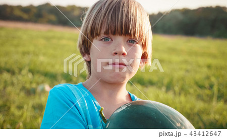 Portrait of farmer's son with whole watermelon at field of farm. 43412647