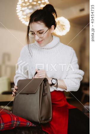 Fashionable woman hold black bag 43454735