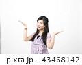 白い背景の前で両手のひらを上に向け上下に広げている笑顔の若い女性 43468142
