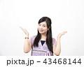 白い背景の前で両手を広げている笑顔の若い女性 43468144