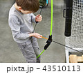 Little boy sets arrow in children's sports bow 43510113
