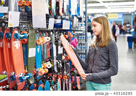 Teenage girl chooses skateboard in sport store 43510295