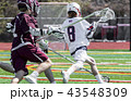 Lacrosse player with ball being chased 43548309