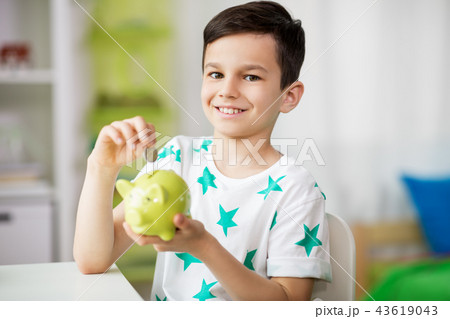 little boy putting coin into piggy bank at home 43619043