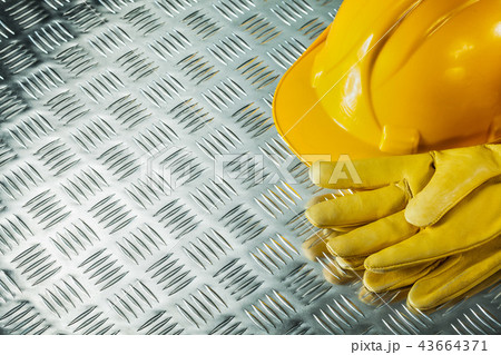 Leather safety gloves hard hat on fluted metal texture 43664371