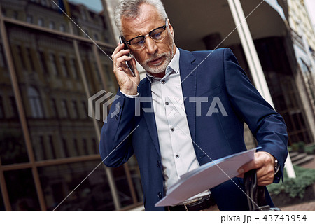 Senior businessman is discussing on the phone a contract outdoors near office 43743954
