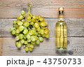 Small bottle of white wine and bunch of grapes 43750733
