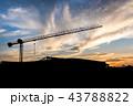 construction cranes over sun at sunrise. 43788822