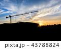construction cranes over sun at sunrise. 43788824