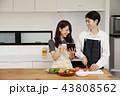 タブレットで献立をネット検索し料理をするカップル 43808562