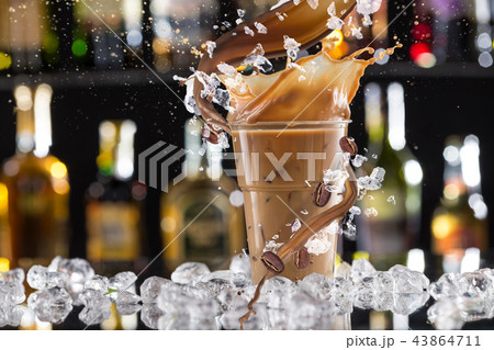 Cold coffee drink with ice, beans and splash. 43864711