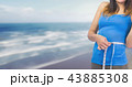 Woman measuring weight with measuring tape on waist on Summer beach 43885308